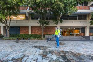 Man using blower on pavement