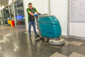 Man near lifts with scrubber at QUT