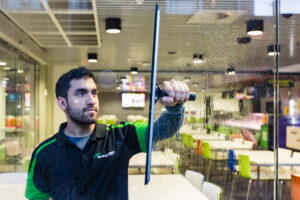 Man cleaning glass blurred background