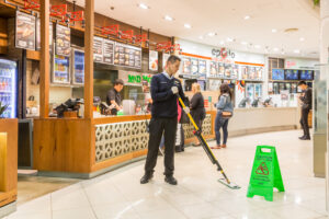 Man Mopping at food court green wet sign