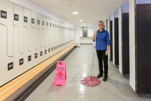 Smiling woman cleaning bathroom with pink wet sign and mop