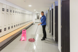 Female mopping in bathroom pink wet sign