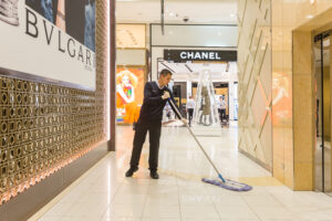 Man mopping at Queens Plaza near Chanel