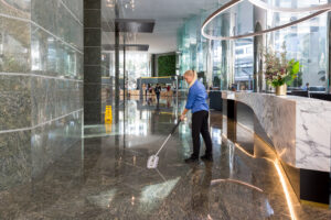 Female dry mopping in main reception area