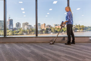From distance Female Vacuuming commercial building