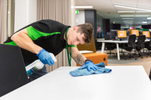 Close up Male Springmount Team member cleaning desks at QUT