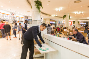 Male Springmount Team member cleaning table in food court
