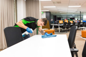 Male Springmount Team member cleaning desks at QUT