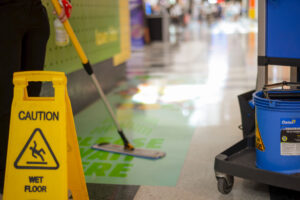 Cleaner mopping floor of shopping centre